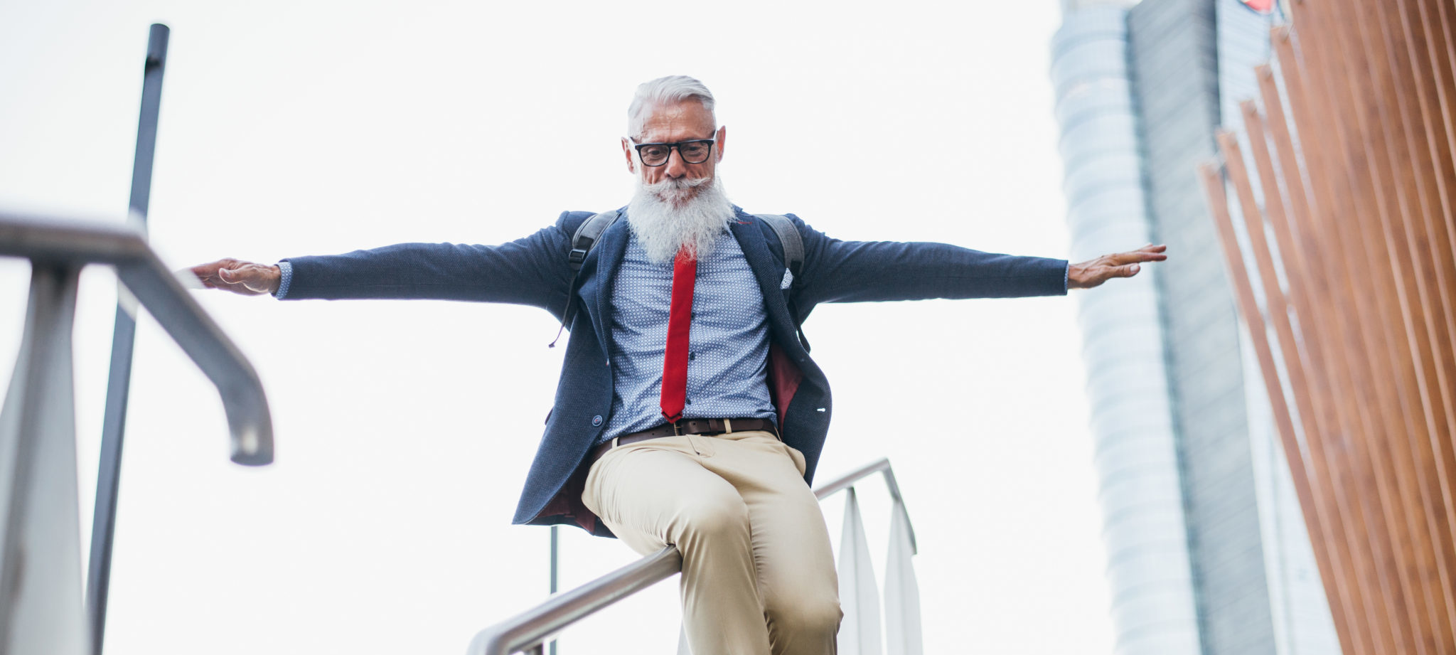 Business man sliding down railing, free from stress of managing his own website