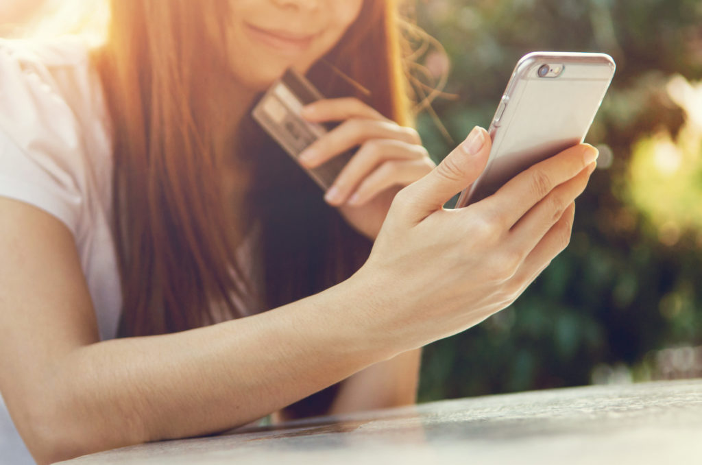 Woman browsing mobile phone with credit card in hand
