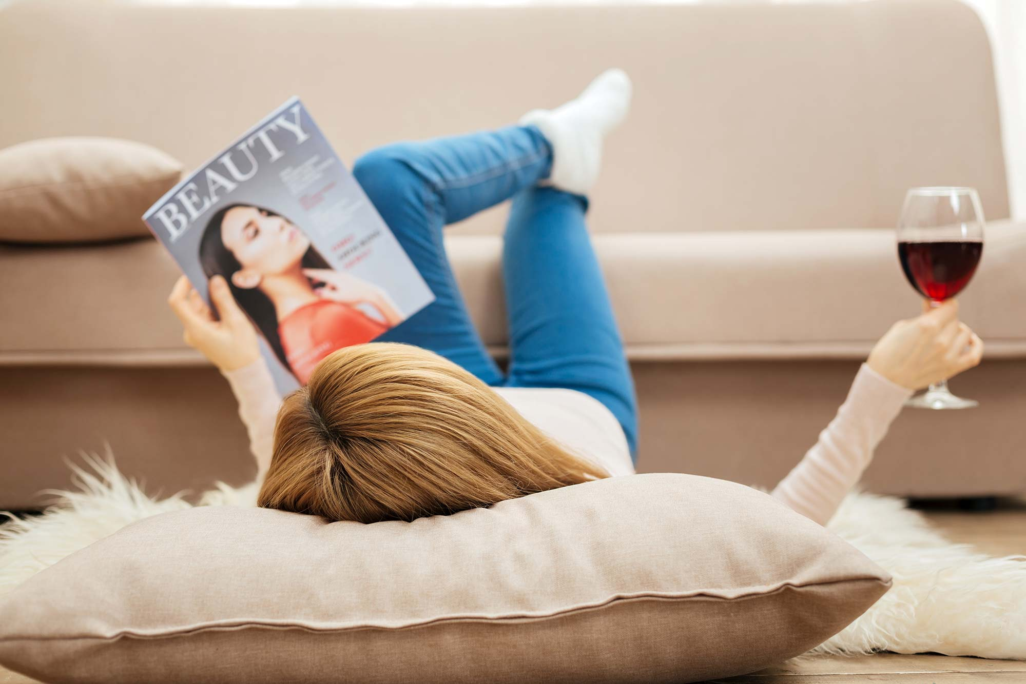 Woman relaxing with wine and a magazine